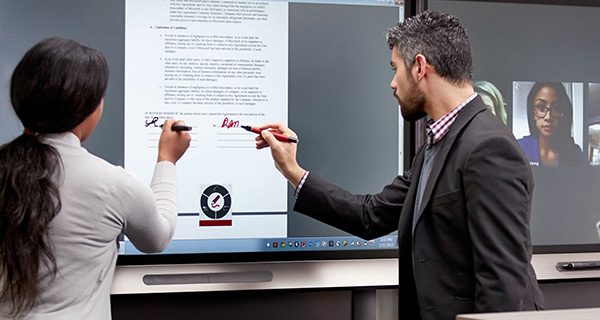 Business staff using a digital whiteboard in a huddle space